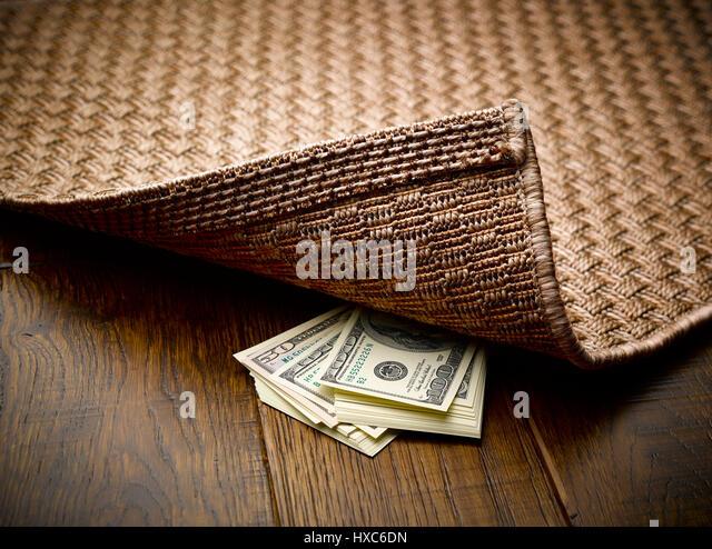 Money hidden under rug - Stock Image