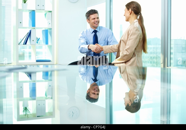 Formally dressed young people handshaking after making agreement in office - Stock Image