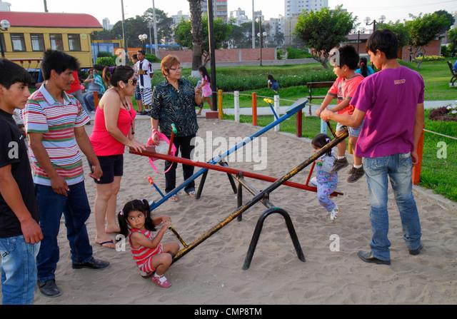 Peru Lima Barranco District Avenida Miguel Grau Parque Municipal public park playground Hispanic man woman girl - Stock Image