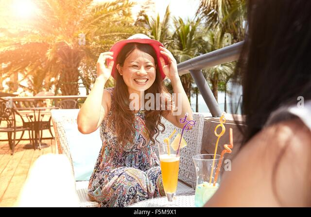 Mid adult woman and daughter having soft drinks at beach cafe, Zhuhai, Guangdong, China - Stock Image