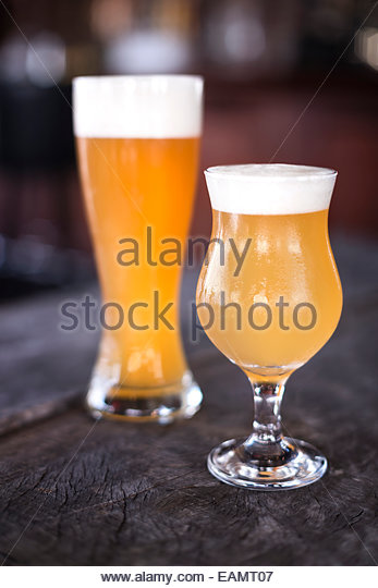 Tulip and weizen glasses of beer on a rustic wood surface with bar in background. - Stock Image