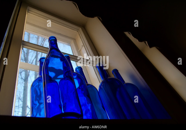 Empty blue bottles on window sill - Stock Image