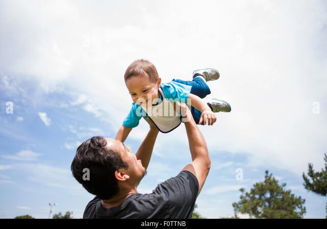 Young man playing lifting up toddler brother in park - Stock Image