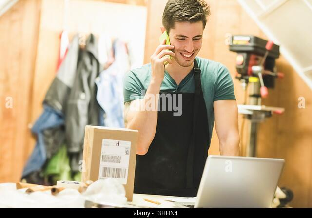 Young man in workshop standing at desk talking on telephone looking at laptop - Stock Image