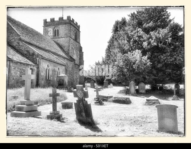 England - Cotswolds - Miserden Church of England exterior view including Graveyard using Monochrome Infrared Effect. - Stock Image