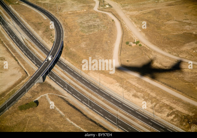 Forms of travel concept - shadow of an airplane flying over a large highway, freeway, motorway - Stock-Bilder