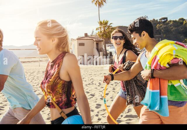 Group of friends walking on beach, ready for picnic - Stock Image