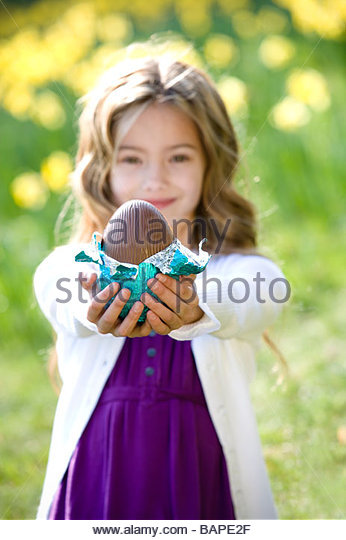 A young girl holding an Easter egg - Stock Image