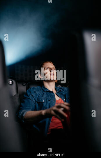 Young man watching movie in theater. Caucasian male watching film in multiplex cinema. - Stock Image