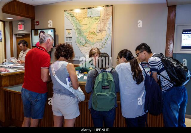 Florida Everglades National Park Ernest Coe Visitor Center Asian woman man couple park ranger information desk map - Stock Image