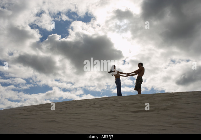 Young couple holding hands on top of sand dune - Stock Image