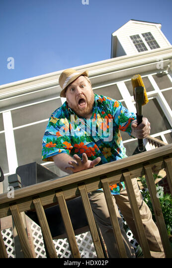 Surprised man  barbecuing on patio - Stock Image