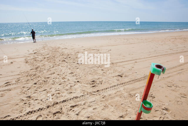 Angler fishing on the beach with rod stand on foreground. Sea angling sport at the beach, Huelva, Spain - Stock Image