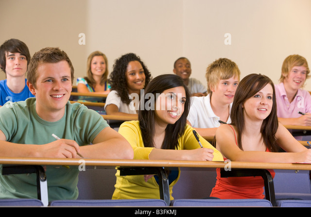 Students in class paying attention and taking notes (depth of field) - Stock Image