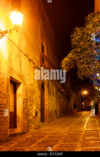 Cobblestone street illuminated by light at night. - Stock Image