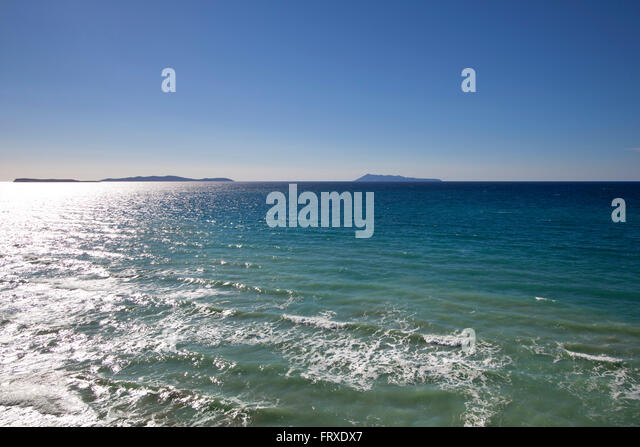 View across the sea at the rocky coast at Cape Drastis, near Peroulades, Sidari to the Diapontic islands, Corfu - Stock Image
