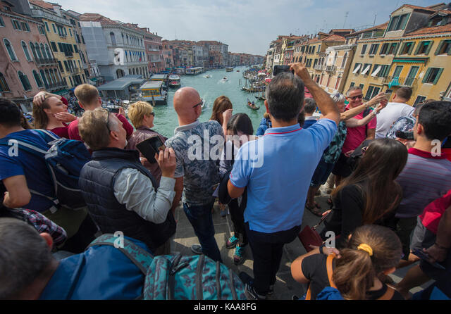 A ridiculously crowded Rialto Bridge in Venice with tourists packed, looking over the Grand Canal - huge pressure - Stock Image