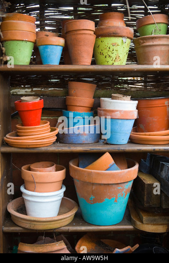 Terracotta pots stacked up on a shelf - Stock Image