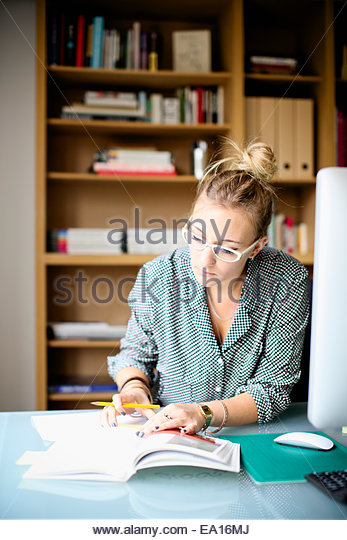 Woman reading and writing in book - Stock Image