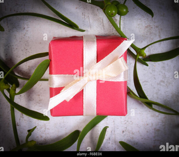 Wrapped red gift for Christmas or other celebration and branch of green mistletoe on old wooden background - Stock Image