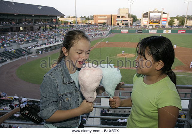 Arkansas North Little Rock Dickey Stephens Park minor league baseball Arkansas Travelers Asian girls eat cotton - Stock Image