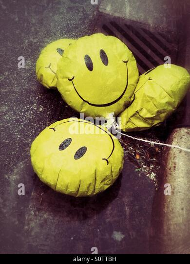 Sad, deflated happy face balloons laying in a puddle on the side of the street - Stock Image