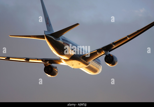 American Airlines Boeing 777 just after take off in reflecting sunset light at Heathrow Airport, London, England, - Stock Image