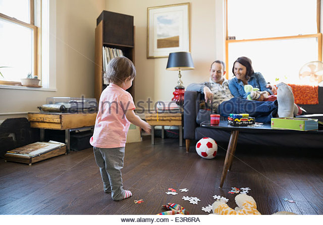 Parents watching baby daughter play with soccer ball - Stock Image