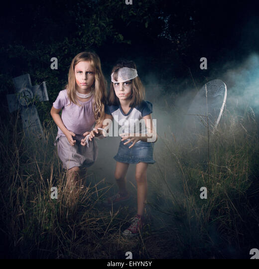 Two girls pretending to be zombies in a cemetery at Halloween - Stock Image