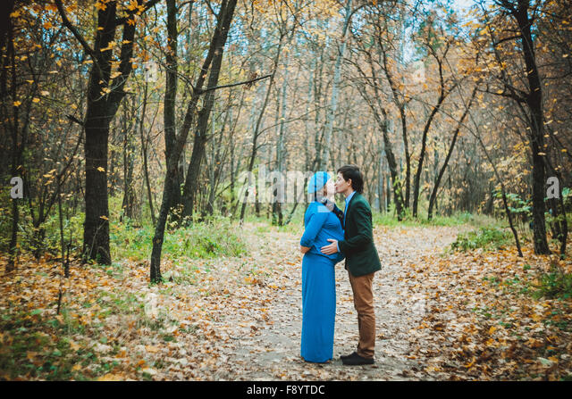 Happy couple husband kissing his pregnant wife in autumn park - Stock-Bilder