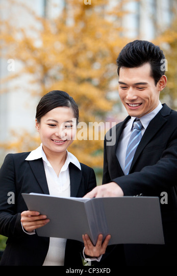 A businessman and businesswoman outside office buildings looking at a document - Stock Image