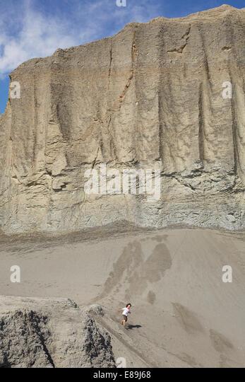 Boy running down giant sand dune - Stock-Bilder