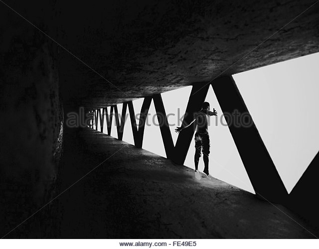 Side View Of Man With Arms Outstretched Standing On Bridge - Stock Image