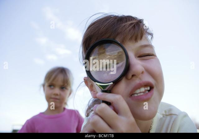 Girl looking through magnifying glass, looking at camera, close-up - Stock Image