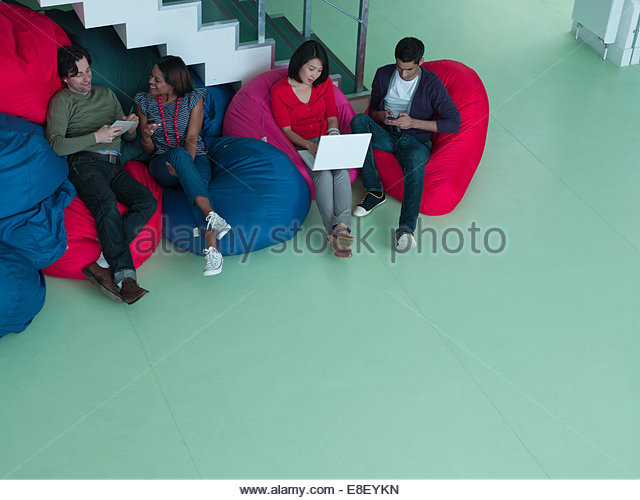 Business people in bean bag chairs looking at laptop - Stock-Bilder