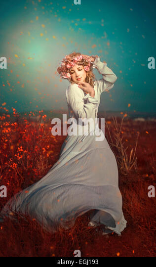 young woman with flower wreath dancing in meadow - Stock Image