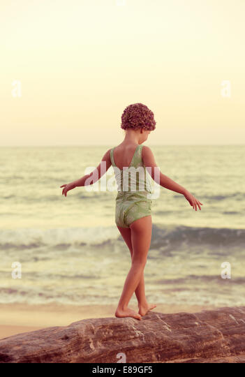 Girl in swimcap walking along oceanside rocks - Stock Image