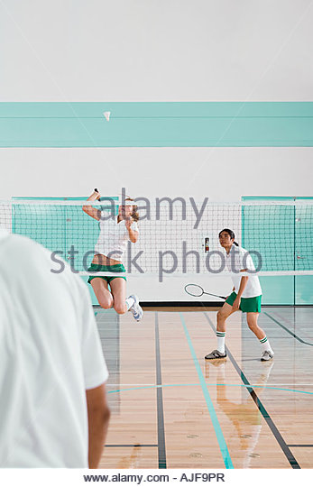 Three people playing badminton - Stock Image