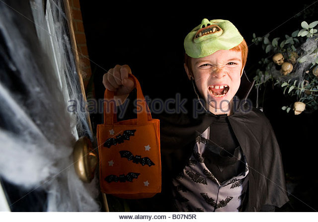 Boy in costume at a Halloween party, holding an orange party bag - Stock Image