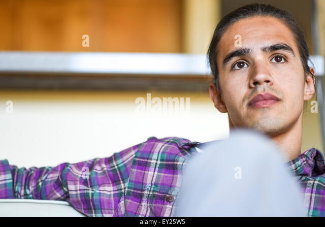 Portrait of young man sitting indoors relaxing - Stock Image