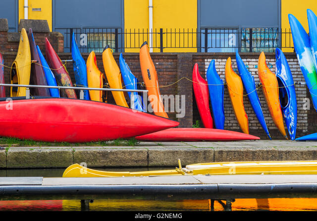 Row of colourful kayaks leaning against brick wall on the Regent?s canal in London - Stock-Bilder