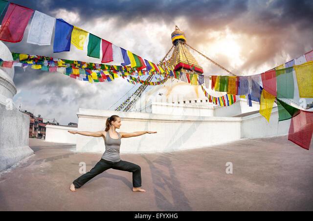 Woman doing yoga warrior pose at Bodnath stupa, Kathmandu, Nepal - Stock Image