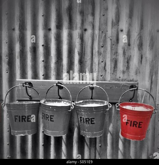 Fire buckets hanging on a wall - Stock Image