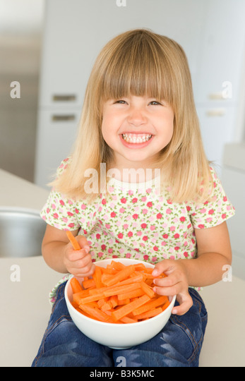 Young girl in kitchen eating carrot sticks smiling - Stock Image