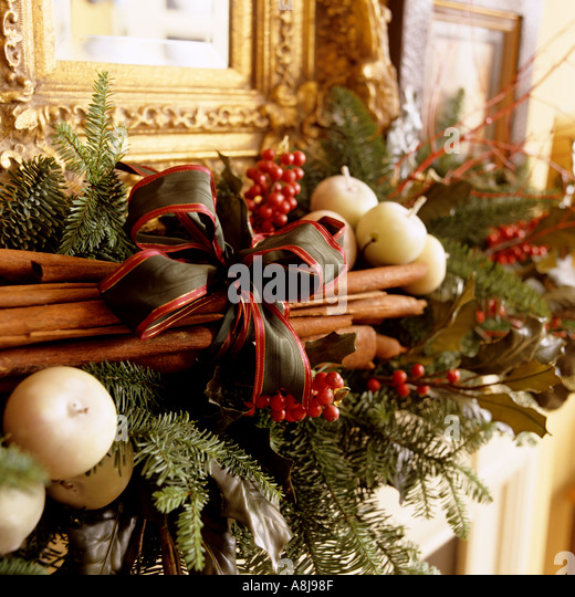 Christmas fireplace decoration with cinnamon, pine and candles - Stock Image