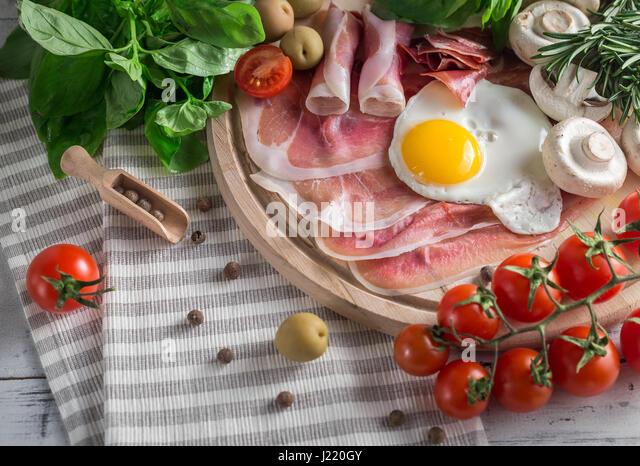 Healthy Mediterranean breakfast groceries: fried eggs, ham, vine tomatoes, mushrooms, basil, olives, rosemary on - Stock Image