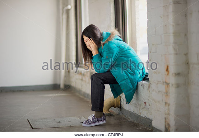 young girl sitting on a window sill with head in hands looking depressed. - Stock Image