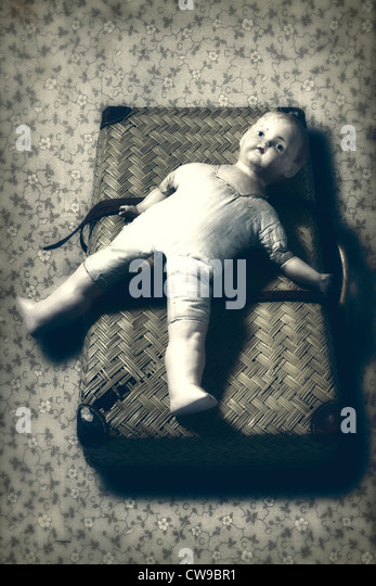 an old, broken doll lies on an old suitcase - Stock Image