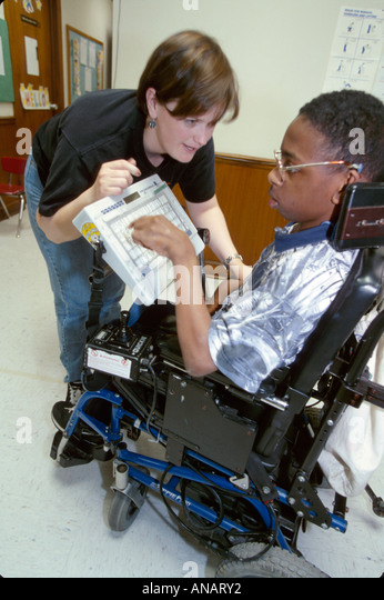 New Jersey East Orange Cerebral Palsy Center disabled student female therapist Black teen wheelchair communicator - Stock Image