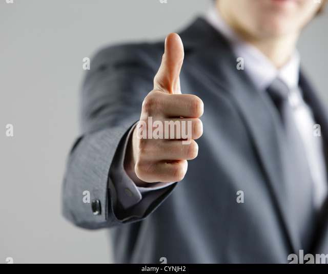 Close-up of a young businessman showing thumbs up. - Stock Image